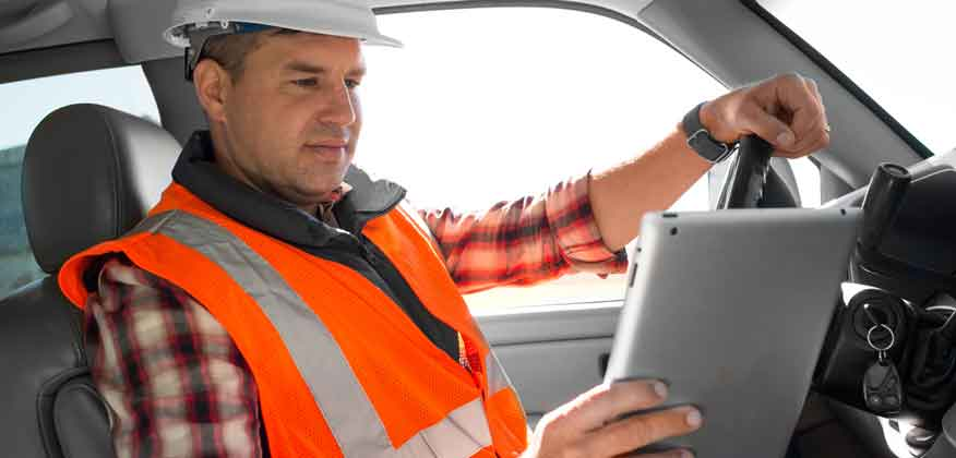 Man in orange construction vest and white hard hats sitting in a vehicle looking at an iPad