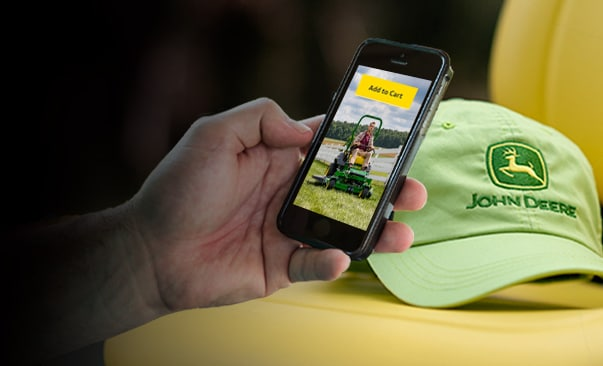 Hand holding mobile device.  On screen display shows a man riding a lawn mower and the yellow button says 'Add to Cart'.  Green John Deere logo hat in the background.